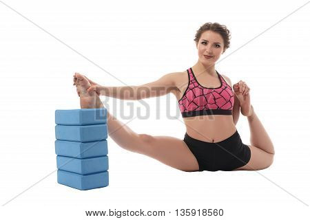Sport. Image of lovely brunette stretching with bricks