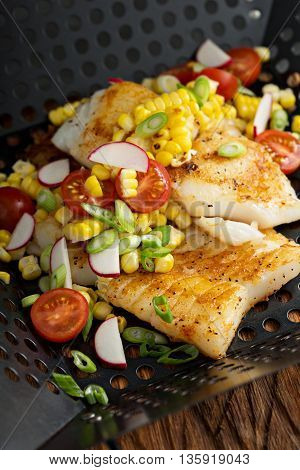 Grilled cod with summer vegetable salad with corn, radishes and tomato