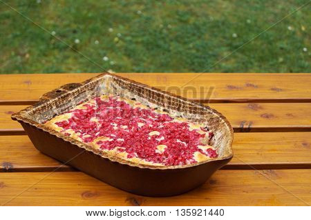 Red currant cake in the pan on a wooden table