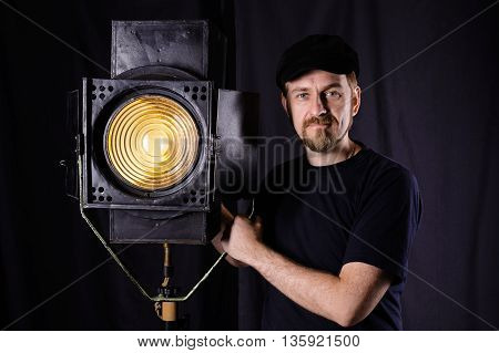 Man Wearing A Cap Stands Near Stage Spotlight