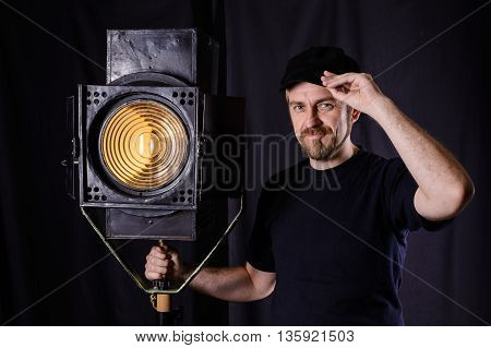 Attractive Bearded Man Hand On The Cap Near Stage Spotlight