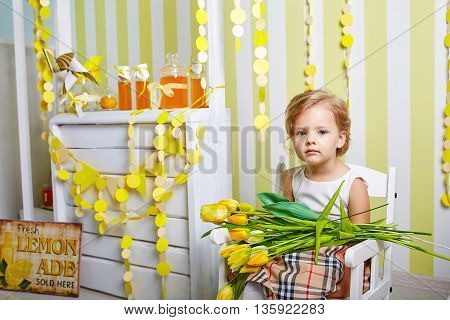 Beautiful little girl.Blue-eyed blonde.White chair.Lemonade.Children's room. Happy small girl portrait.