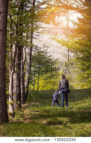 Mother walks in the forest with a child