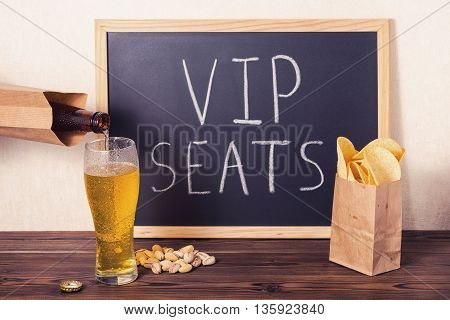 вeer Is Poured Into Glass, Chips, Pistachio And Handwriting Text Vip Seats Written In Chalkboard Ove