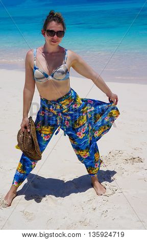 Beautiful woman on the beach with hat against the sand. Beautiful pants in the style caribbean
