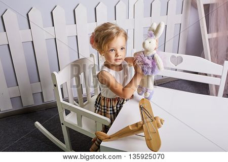 Beautiful little girl playing toys.Blue-eyed blonde.White chair.Children's room. Happy small girl portrait.