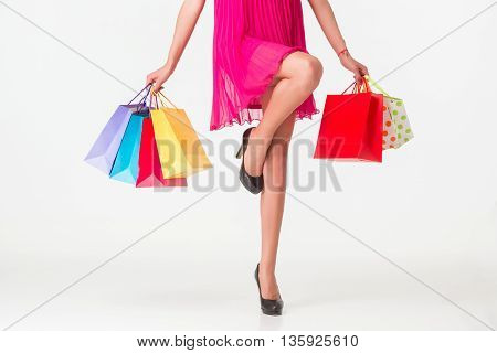 Happy shopping. Unrecognizable woman in red dress holding multicolored shopping bags