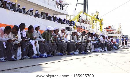 Messina , Sicily - June 26, 2016: Migrants disembark from Aquarius ship more than 655 men, women and children . In the picture the newly landed immigrants are awaiting identification.