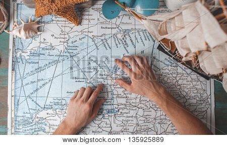 Man's Hand On Map On Desk With Traveller Attributes