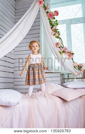 Beautiful little girl jumping on bed. Blue-eyed blonde.Children's room. Happy small girl portrait.