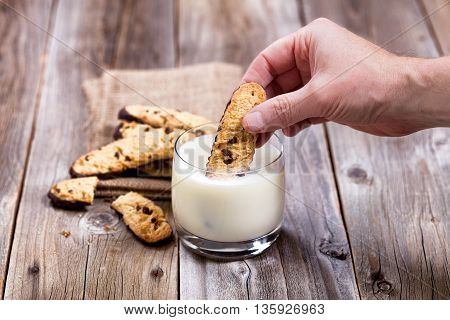 Close up of hand dipping chocolate chip cookie into glass of milk. Selective focus on thumb and cookie. Additional cookies on linen cloth with rustic wood underneath.