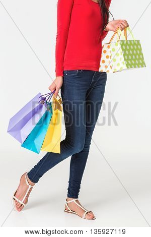 Happy shopping. Unrecognizable woman in jeans and a red shirt holding multicolored shopping bags