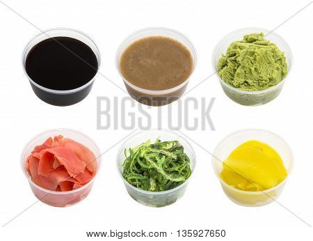 Soy sauce, wasabi, pickled ginger, Chuka, sesame sauce and pickled radishes in small bowl isolated on white background