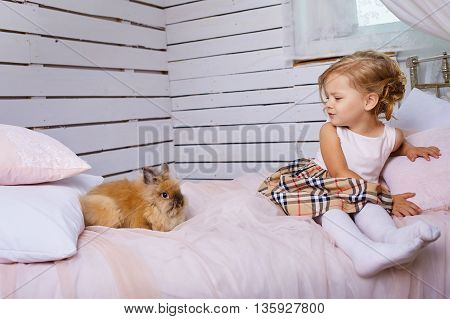 Beautiful little girl playing with rabbit.Blue-eyed blonde. Children's room. Happy small girl portrait.