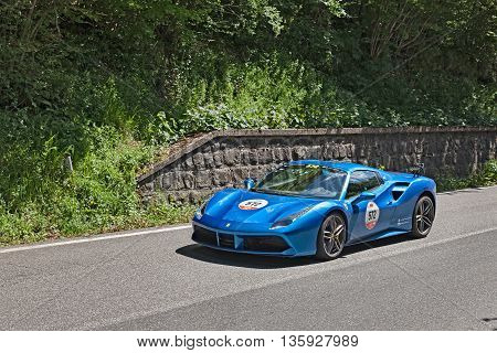 PASSO DELLA FUTA (FI) ITALY - MAY 21: driver and co-driver on a sports car Ferrari 488 Spider (2016) in rally