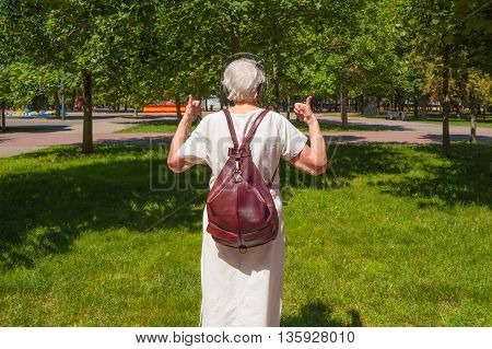 The back view of senior gray woman with earphones showing thumbs up in the park