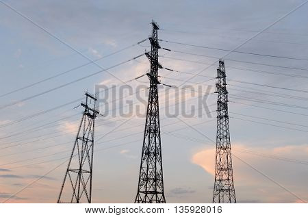 Transmission line on background of cloudy sky at evening.