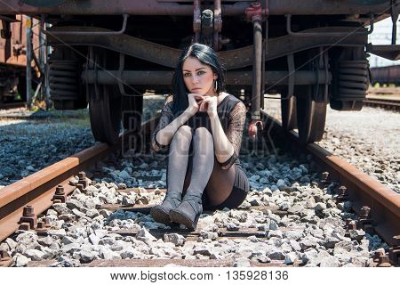 Young beautiful girl in black dress and nylons sitting on rail tracks, cargo wagons in background, emotive portrait