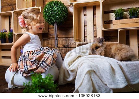 Beautiful little girl playing with rabbit.Blue-eyed blonde.Children's room. Happy small girl portrait.