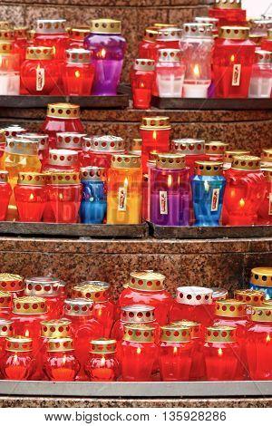 Votive candles glows on a grave, lantern