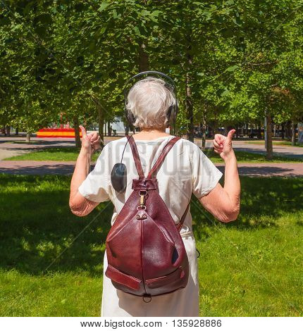 The back view of senior gray woman with earphones and computer-mouse showing thumbs up in the park