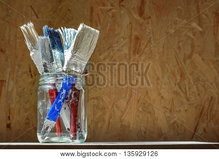 Old paint brushes in a glass jar on wooden panel background