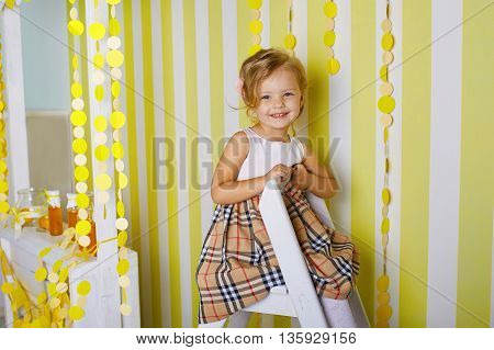Beautiful little girl sitting on step ladder.Blue-eyed blonde.Children's room. Happy small girl portrait.
