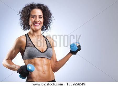 Fit woman lifting weights on gray bakground