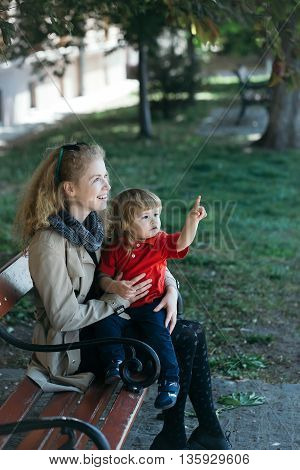 Girl Holds The Little Boy Who Points At Something