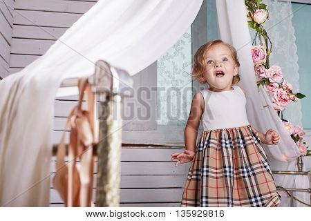 Beautiful little girl. Blue-eyed blonde.Children's room. Happy small girl portrait.