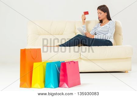 online shopping and technology concept - smiling beautiful young woman with tablet pc computer and credit card. She sit on sofa with colorful bags