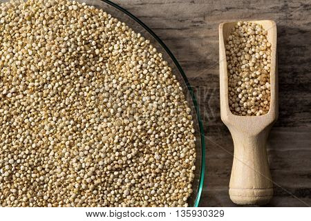 Quinoa in glass dish on wooden background with spice shovel detail view from above.