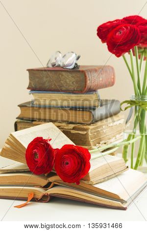 Stack of vintage books with red ranunculus flower