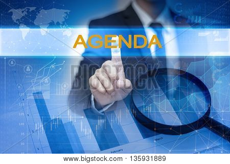 Businessman hand touching AGENDA button on virtual screen