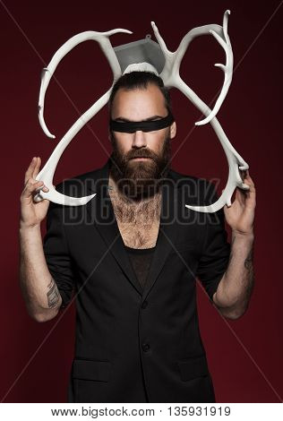 Brutal bearded man with horns. On red background. Man in black suit. fashion studio shot.