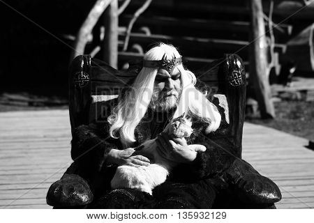 Druid old man with long grey hair beard with crown in fur coat holds cat and sits in wooden chair black and white on log house background