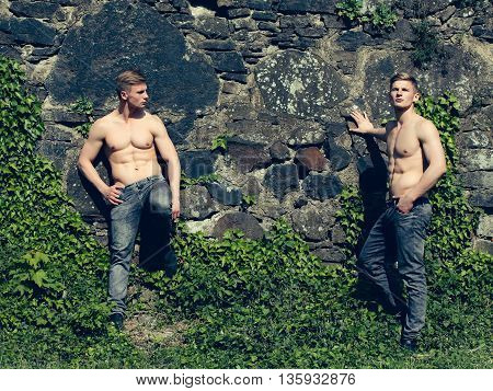 Muscular young twins with beautiful sexy body and bare torso standing outdoor on masonry wall background with vine