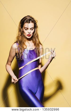 Attractive slim girl with long hair in violet second skin jumpsuit standing with tape-line around waist on yellow background