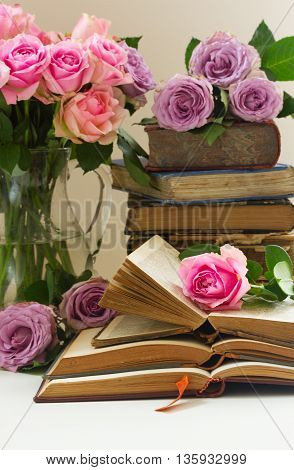 Pile of old books with bouqet of pink and violet fresh rose flowers