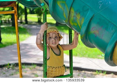little four-year-girl in a yellow dress and beautiful yellow cap resting in a break between games. a children's playground . hot summer day. Kiev. Ukraine