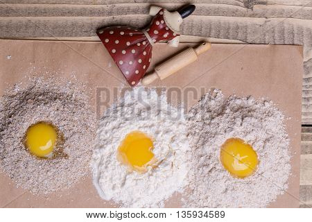 Three eggs broken on heaps of white and whole wheat flour bran with red dress porcelain figurine toy culinary utensils rolling pin on timber background