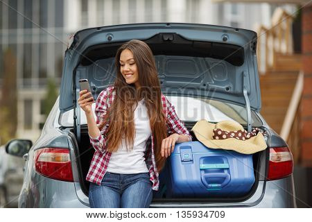 Beautiful young brunette woman with long straight hair and brown eyes,a nice smile,the right hand wearing the ring,dressed in a plaid shirt and blue jeans,sitting in the open trunk of the gray car next to the blue suitcase,read SMS message