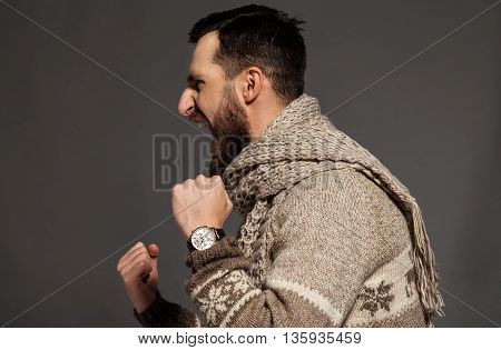 Unleashing his emotions. Side view of furious young bearded man shouting while standing against grey background