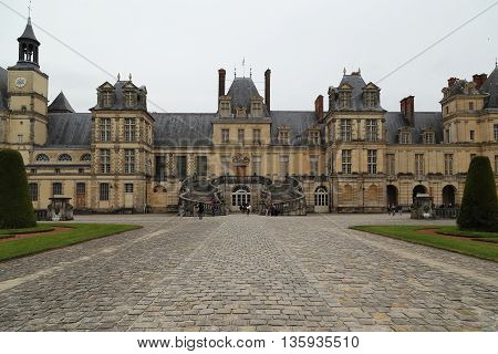 FONTAINEBLEAU, FRANCE - MAY 16, 2015: This is the main entrance to Fontainebleau castle with a staircase-horseshoe.