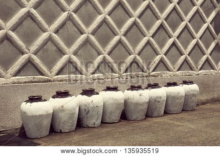 row of traditional Japanese ceramic sake bottles close to the ancient building wall