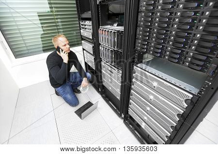 It engineer or technician monitors and solving problems with servers and network equipments in data rack. Shot in datacenter.