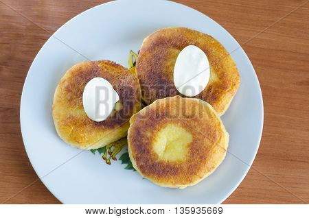 Grandma's curd pancakes with their hands with scented cream