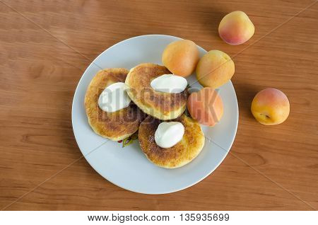 Grandma's curd pancakes with their hands with scented sour cream and sweet apricots