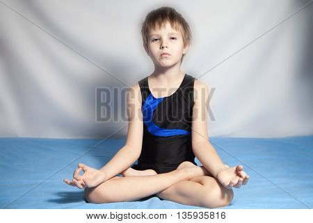 The young boy which is practices yoga