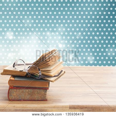 Stack of Books and glasses on wooden table desktop border, copy space on bokeh polka dot background